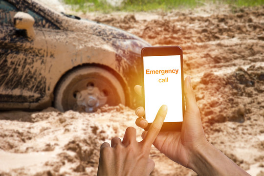 Man hand using smartphone calling emergency for help car tire stuck in the mud background. Car wheel in the mud clay can not run out.