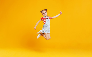 funny child girl jumping on colored yellow background