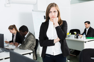 Tired businesswoman standing in office on backround with colleagues