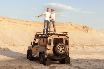 Man and a woman travel by car in the desert.