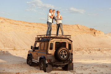 Family with a small child travels by car in the desert among the barkhans.