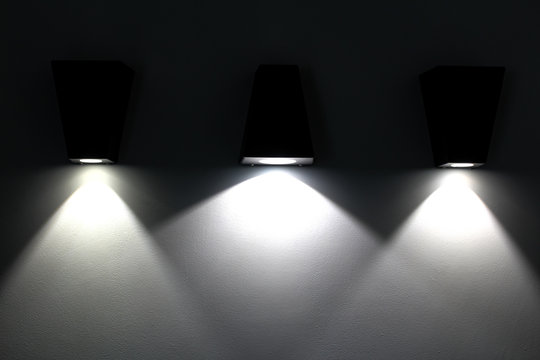 Three lamps light up a wall..