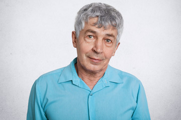 Portrait of attractive mature male with serious look, listens his grandson with great interest, dressed in shirt, poses against white concrete wall. Confidnet elderly man enjoys spare time at home