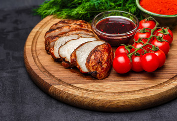 whole and sliced chicken breast with spices on a stone board, top view copy
