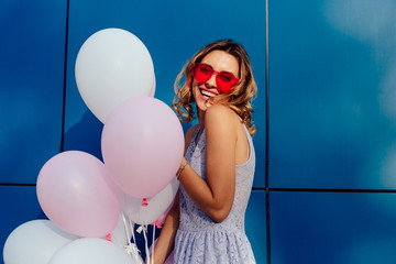 Holiday concept. Beautiful funny girl posing at camera with balloons, smiling widely, wearing stylish sunglasses. Dressed in summer dress.