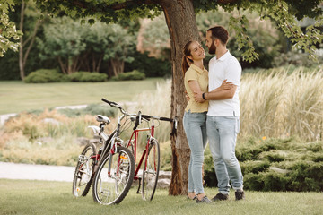 Beautiful young couple in a romantic hug. Young man and woman hugging and looking on each other on summer nature background. Romantic summer vacation.