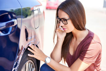 Young woman making phone call to insurance agent while inspecting scratched car