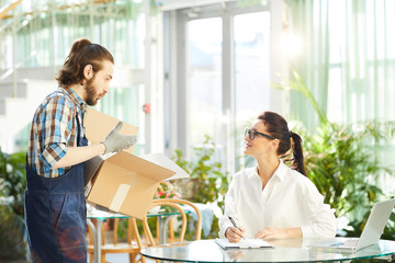 Content confident attractive young female logistics manager with pony tail inspecting delivered goods and keeping records in paper while working with bearded mover showing product