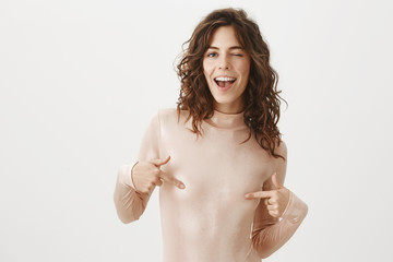 Free nipple. Portrait of carefree and confident joyful female with curly hair, covering nipples with fingers, smiling broadly and winking with flirty expression, being in sensual and romantic mood