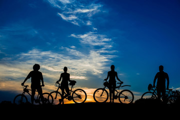 Silhouettes of cyclist on beautiful evening sky background. Group of friends with bikes on sunset sky background. Enjoying of beauty.