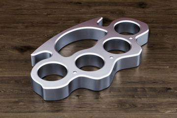 Brass knuckles on the wooden table, 3D rendering