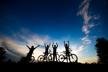 Cyclists with raised hands at sunset sky. Group of friends with bikes standing on hill at evening sky background. Enjoying of beauty.