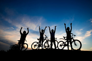 Cyclists resting on hill at sunset sky. Group of young people standing with raised hands on hill on evening sky background. Carefree and freedom.
