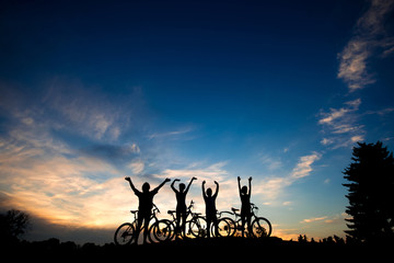 Friends with bikes at sunset background. Silhouettes of cyclists resting on evening sky background. Amazing summer evening scenery.