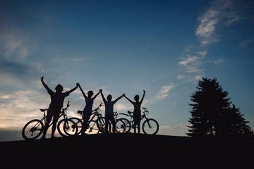 Group of cyclists holding hands together at sunset. Silhouettes of young persons with bikes standing on meadow and holding hands at evening sky.