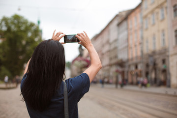 Tourist walking through the city center and taking photo on her mobile phone. Space for text