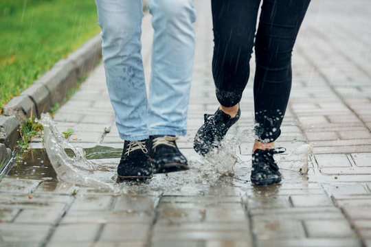 Young couple walking in the rain on puddles