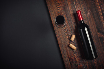 Bottle of wine corks and wineglass on rusty background