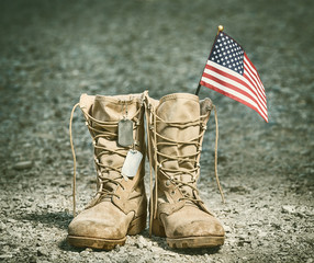 Old military combat boots with the American flag and dog tags. Rocky gravel background. Memorial Day or Veterans day concept. Vintage tone.
