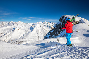 Young happy skier sitting on the top of mountains and enjoying view of Rhaetian Alps, Tonale pass, Italy, Europe