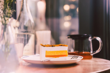Piece of raw vegan mango coconut cake on wooden table at the restaurant. Food photography concept. Warm tones filter effect, vertical