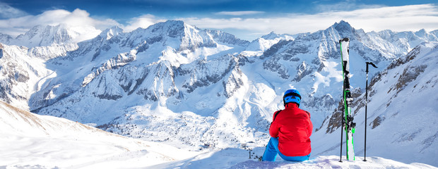 Fototapete - Young happy skier sitting on the top of mountains and enjoying view of Rhaetian Alps, Tonale pass, Italy, Europe