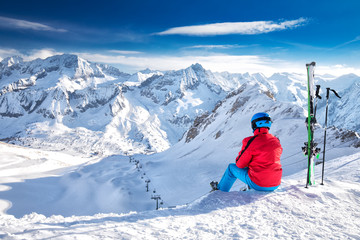 Fototapete - Young happy skier sitting on the top of mountains and enjoying view of Rhaetian Alps, Tonale pass, Italy, Europe.