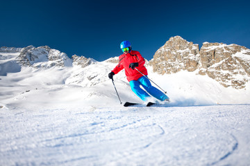 Fototapete - Man skiing on the prepared slope with fresh new powder snow.