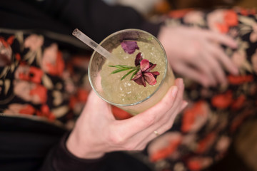 Hands of woman in stylish trousers holding her decorative cocktail in a bar