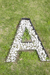 Letter A built from white stones on green grass as seen from high above