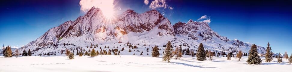 Wall Mural - Stunning winter sunrise over Adamello, Presanella mountains from Tonale town, Italian Alps, Europe.
