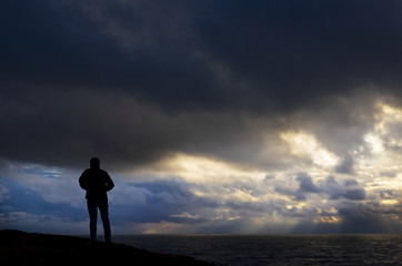 Man with a jacket on the top of the mountain with the sea in the background and cloudy weather
