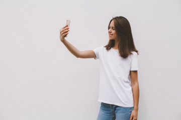 Smiling happy hipster girl wearing a casual white t-shirt and taking selfie while standing on a white concrete wall background