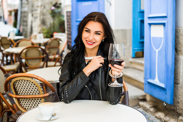 A young beautiful girl in a summer dress and a black leather jacket. Sits in a vintage European cafe on the street and drinks wine, travel old Europe, weekend