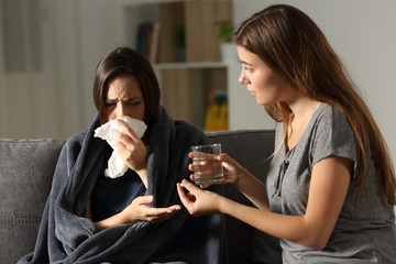 Sick woman and her friend giving painkiller pill