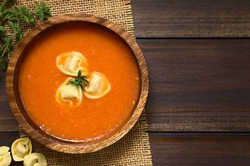 Hausgemachte frische Tomatencremesuppe mit Tortellini und frische Oreganoblätter, fotografiert mit natürlichem Licht (Selektiver Fokus, Fokus auf die Suppe)