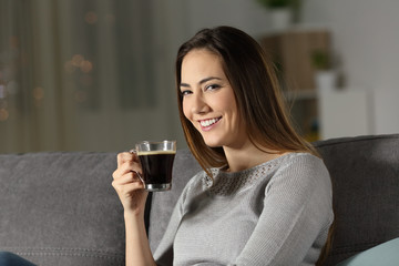Woman holding coffee cup in the night looking at you