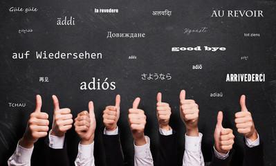 """viele Daumen Hoch und """"Auf Wiedersehen"""" in vielen Sprachen auf Kreidetafel"""