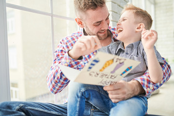 Adorable little boy and his bearded dad having fun together while reading handmade greeting card for Fathers Day aloud, panoramic window on background