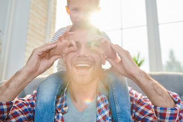 Family portrait of cute little boy sitting on shoulders of his joyful dad and playing funny game while spending Sunday at home, lens flare