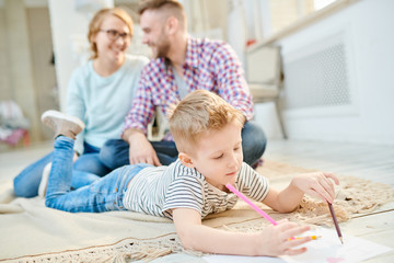Young parents sitting on carpet of modern living room and looking at each other with wide smiles while their adorable little son wrapped up in drawing colorful picture.