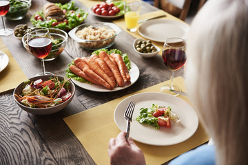 Close up of mature female sitting at table. She is having salad and red wine. Wooden board is full of tasty dishes