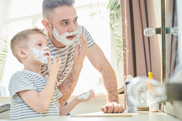 Handsome young man and his little son with shaving foam on their faces having fun together at spacious bathroom with panoramic window