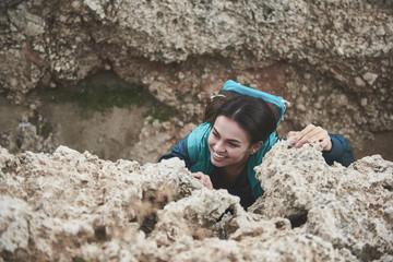 Only up. Top view of cheerful girl mountaineering and smiling. She is holding on to a stone with effort. Climber is laughing