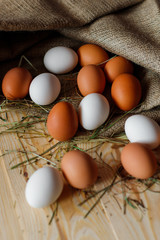 Fresh, raw eggs lie on the grass. Wood background. Texture of burlap. Organic background. Healthy eating. Easter composition