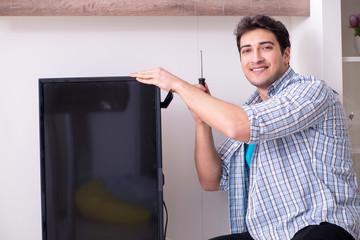 Man repairing broken tv at home