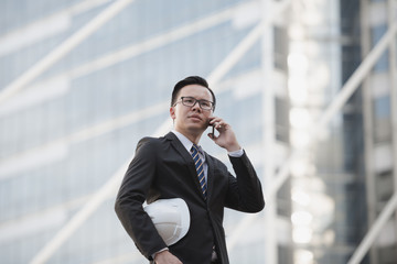 Portrait of a young asian businessman talking on mobile phone and holding a helmet. Man outdoor with phone in a city Bangkok Thailand. Concept of communication