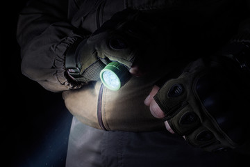 Photo of a male person in brown tactical outfit jacket and gloves using green tactical led flashlight.