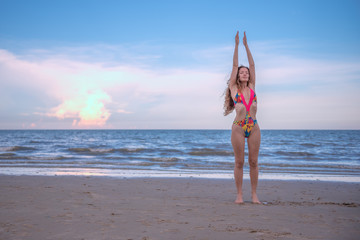 Young healthy woman with blonde curly hair doing yoga on the beach, heathy and relaxing concept.