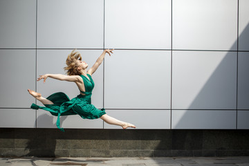 Beautiful girl dancing in the city and jumping against the wall background.